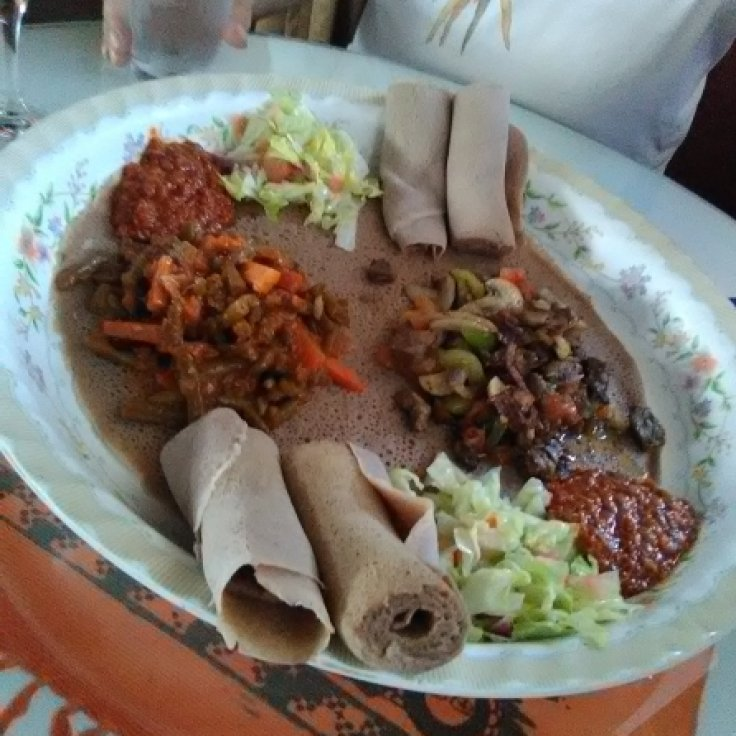 Typical Ethiopian dinner for two, served on a large pancake. Vegetarian entree to the left, meat entree to the right.